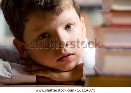 Close-up of little boyâ??s face with pile of books near by looking at camera - stock photo