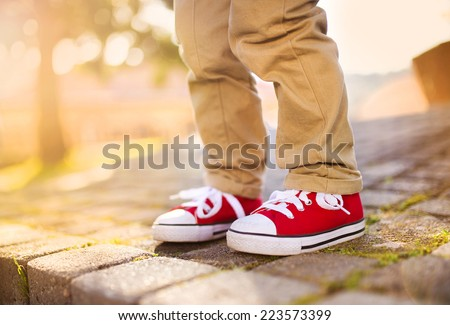 Close-up of little boy standing on tiled pavement in summer park - stock photo