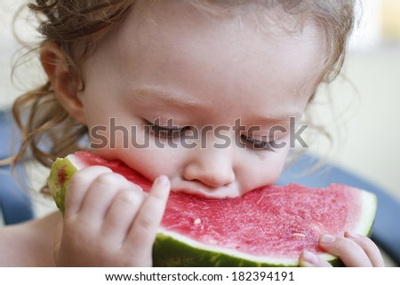 Close-up of little child eating melon - stock photo