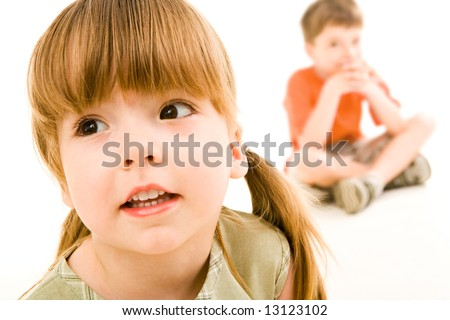 Close-up of little curious girl looking slightly aside on the background of sitting boy - stock photo