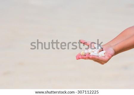 Close up of little girl hand holding beautiful sea shells - stock photo