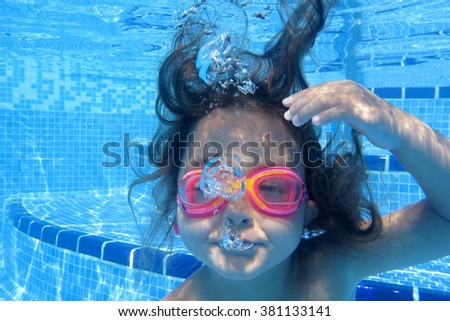 Close-up of little girl looking at camera underwater