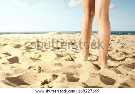 Close up of  little girl walking on the beach towards the ocean with copy space - stock photo