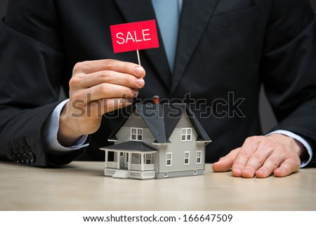 Close up of little home and hand keeping sale tablet. Concept of deal and real estate - stock photo