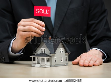 Close up of little house and hand keeping sold tablet. Concept of deal and real estate - stock photo
