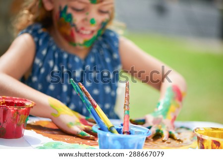 Close up of little painting with hands covered in multicolored paint selective focus - stock photo