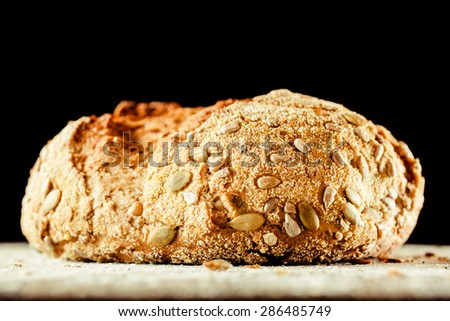 Close Up of Loaf of Artisinal Whole Grain Bread Covered with Pepita Pumpkin Seeds on Floured Surface with Black Background - stock photo