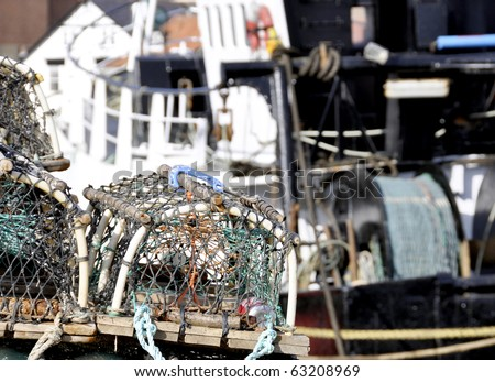Close up of lobster baskets with trawler fishing boat - stock photo