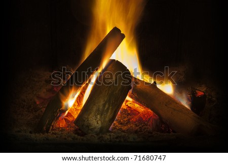 Close up of logs and flames in fire place - stock photo