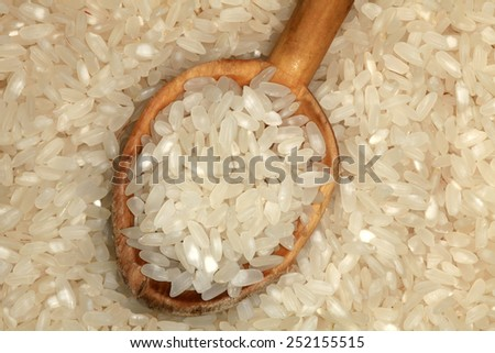 Close up of long white rice in a wooden spoon. - stock photo