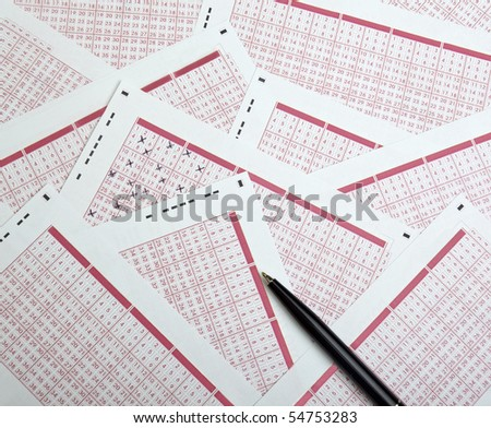 close up of lottery ticket and pen - stock photo