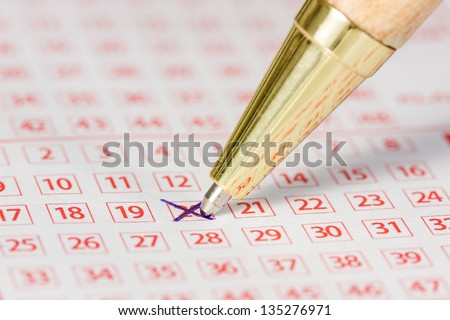 Close up of lottery ticket with a marked number and a pen - stock photo