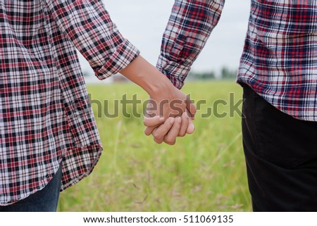 Close Up of loving couple holding hands while walking meadow field.