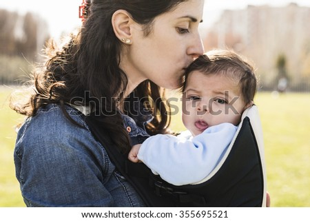 Close-up of loving mother kisses her little baby. Outdoors. Summertime