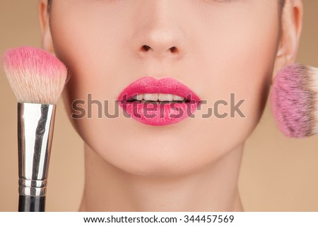 Close up of lower part of the face of young woman. She is getting blush on her cheeks with two brushes - stock photo