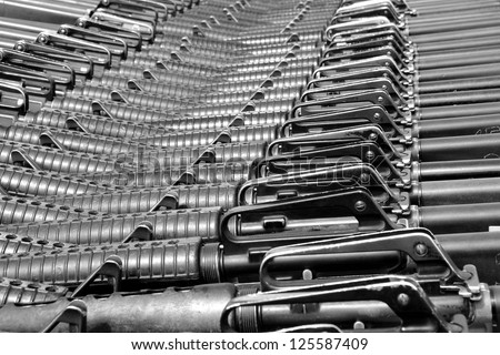 Close-up of M16 rifles stacked in series. B&W - stock photo
