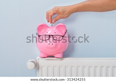 Close-up Of Ma's Inserting Coin In Piggy Bank Kept On Radiator - stock photo