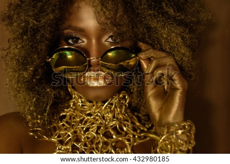Close-up of magic golden african american female model in massive sunglasses with bright glitter makeup, glossy hairstyle and big red lips posing on the studio background - stock photo