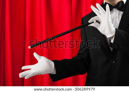 Close-up Of Magician In Suit Showing Trick With Magic Wand - stock photo