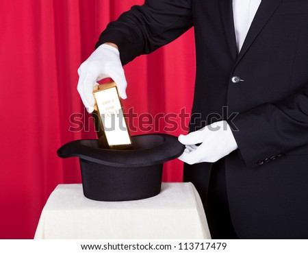 Close-up Of Magician Removing Bullion From Hat - stock photo