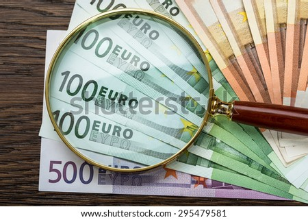 Close-up Of Magnifying Glass Over Euro Banknote - stock photo