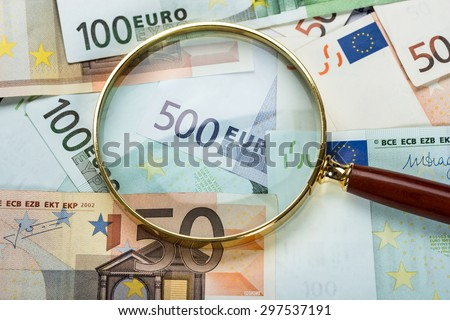Close-up Of Magnifying Glass Over Euro Banknote