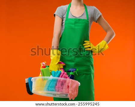 close-up of maid holding cleaning supplies, on orange background - stock photo