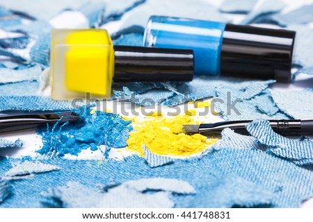 Close-up of makeup brushes, crushed compact blue and yellow eyeshadow with nail polishes of the same colors surrounded by rags of denim. Side view, shallow depth of field - stock photo