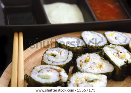 Close-up of maki sushi rolls arranged on a plate with chopsticks, dips blurred in background.