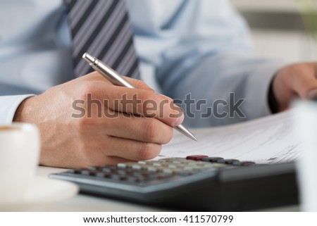 Close up of male accountant making calculations. Man writing something sitting at his office. Partnership agreement, contact signing, closing balance, making financial report or economy concept - stock photo