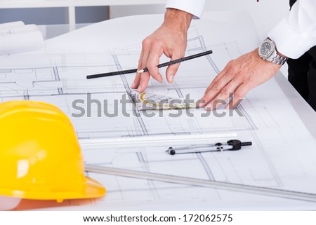 Close-up Of Male Architect Drawing Blueprint In Office - stock photo