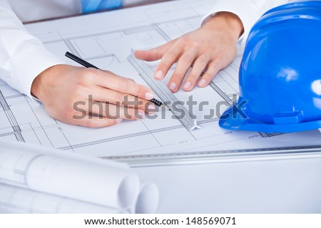 Close-up Of Male Architect Working On Blueprint At Desk - stock photo