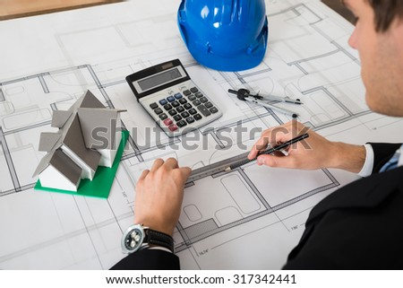 Close-up Of Male Architect Working On Blueprint In Office - stock photo