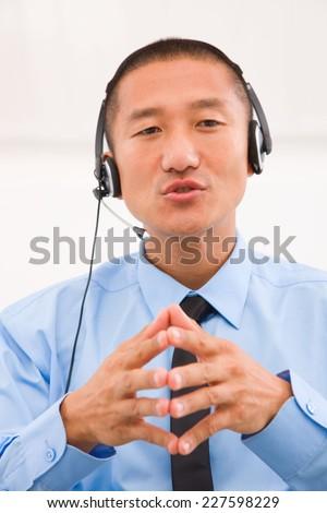 Close-up of male customer service representative wearing headset - stock photo
