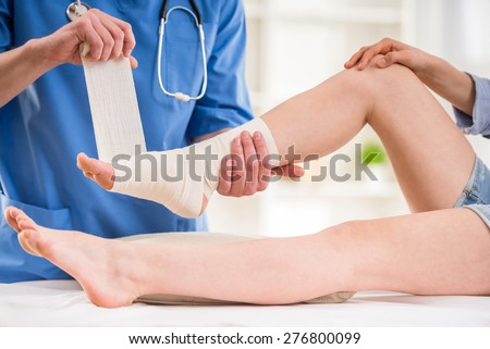 Close-up of male doctor bandaging  foot of female patient at doctor's office. - stock photo