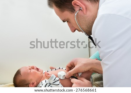 Close-up Of Male Doctor Examining Crying Baby - stock photo