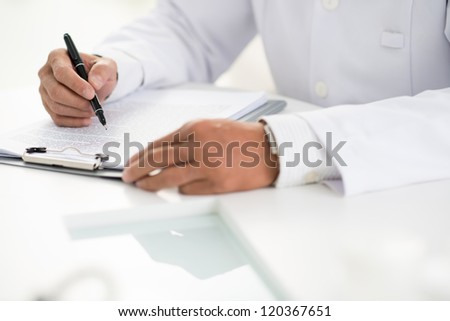 Close-up of male doctor hands with pen over medical document - stock photo