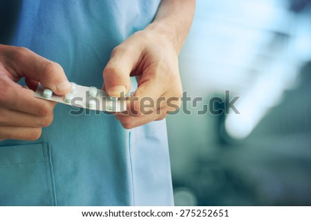 Close up of male doctor holding  pills - stock photo