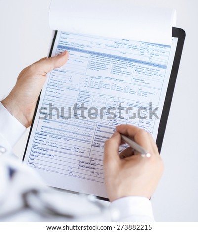 close up of male doctor holding prescription paper in hand - stock photo