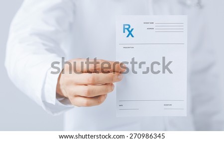 close up of male doctor holding rx paper in hand - stock photo