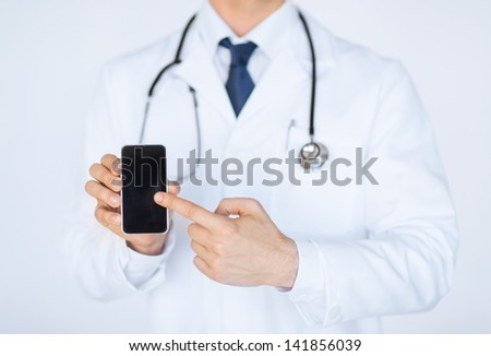 close up of male doctor pointing at smartphone - stock photo