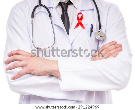 Close-up of male doctor with stethoscope and red AIDS ribbon. - stock photo