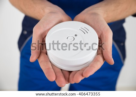 Close-up Of Male Electrician Hand Holding Smoke Detector - stock photo