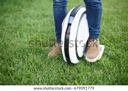 Close-up of male feet in casual shoes and jeans riding hover board outdoors on green grass in summer park. Ecological  transportation technology, self balancing electric board