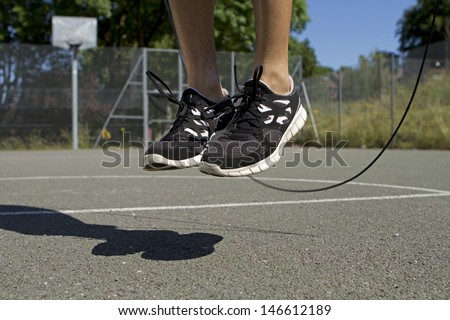Close up of male feet jumping in mid air whilst using a Skipping Rope - stock photo