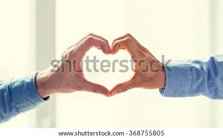 close up of male gay couple hands showing heart - stock photo