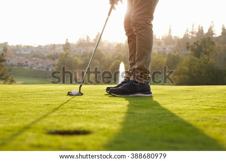 Close Up Of Male Golfer Lining Up Putt On Green - stock photo