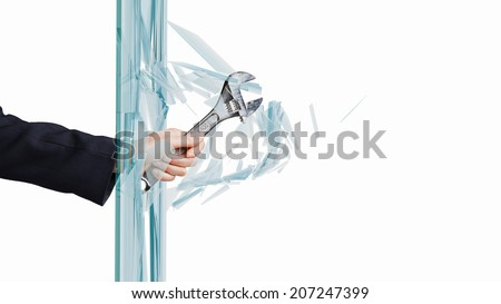 Close up of male hand breaking glass with wrench - stock photo