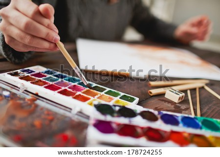Close-up of male hand drawing with water-colors - stock photo