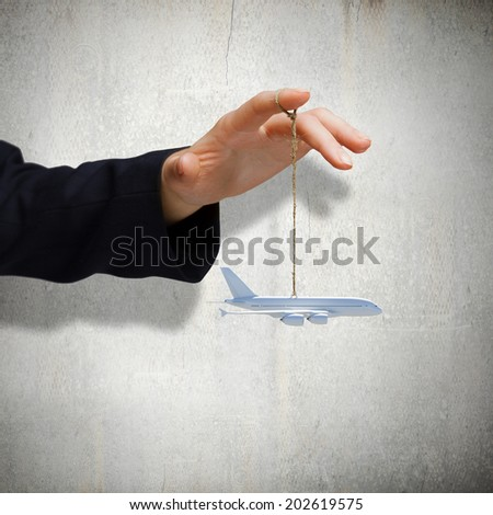 Close up of male hand holding airplane model on rope - stock photo